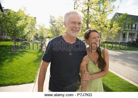 Smiling, affectionate senior couple walking arm in arm on sunny neighborhood sidewalk - Stock Photo