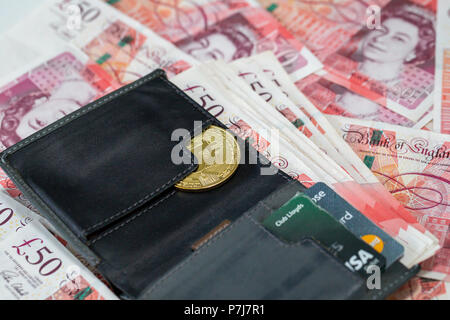 A wallet containing a bitcoin and 50 pound sterling bank notes on a large pile of more fifty pound used banknotes - Stock Photo