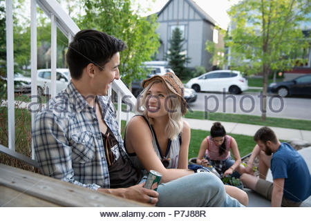 Smiling couple taking a break from gardening with friends on front stoop - Stock Photo