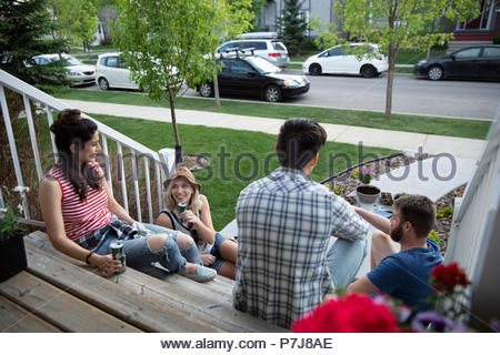 Couples taking a break from gardening, relaxing on front stoop - Stock Photo
