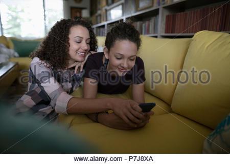 Smiling teenage girls texting with smart phone on sofa - Stock Photo