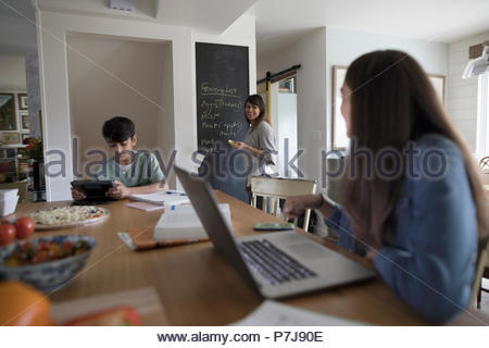 Mother writing grocery list on blackboard in kitchen while tween daughter and son do homework - Stock Photo