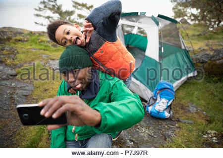 Playful father and son making faces, taking selfie at campsite - Stock Photo