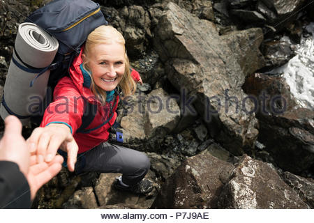 Smiling active senior woman backpacking, reaching for helping hand on rocks - Stock Photo
