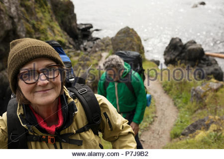 Portrait smiling, confident active senior woman backpacking with husband above ocean - Stock Photo