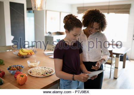 Mother and daughter using digital tablet, cooking pizza in kitchen - Stock Photo