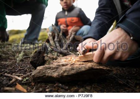 Man preparing campfire in woods - Stock Photo