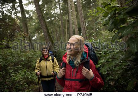 Smiling, carefree active senior women hikers hiking in woods - Stock Photo