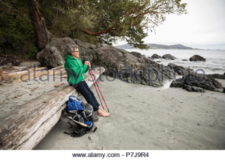 Thoughtful active senior man backpacking, resting on rugged beach - Stock Photo