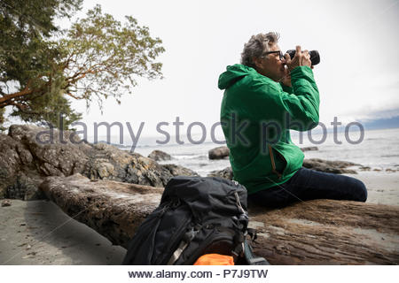 Active senior male backpacker using camera on rugged beach - Stock Photo