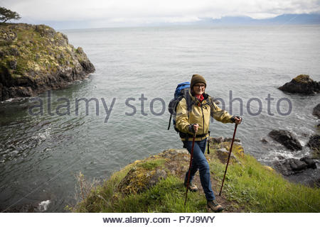 Portrait active senior woman backpacking on cliff with scenic ocean view - Stock Photo