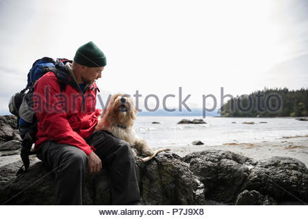 Man with dog sitting on rocks on rugged beach - Stock Photo