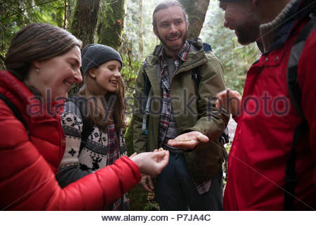 Trail guide and family hiking, exploring in woods - Stock Photo