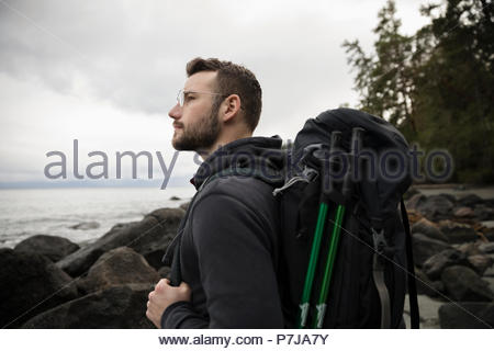 Thoughtful male backpacker on rugged beach - Stock Photo