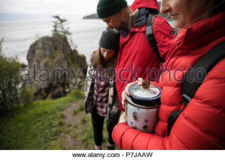 Family with urn spreading ashes on cliff overlooking ocean - Stock Photo