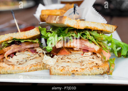 Delicious turkey club sandwich on toast with bacon, lettuce and tomato. - Stock Photo