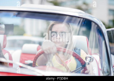 American tourists enjoy a driving tour of Havana by a Cuban-Armenian  guide in his classic 1950's Chevrolet convertible. - Stock Photo