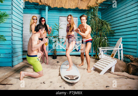 Group of five friends celebrating in their summer beach house - Stock Photo