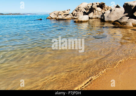 a view of the clear water of the Mediterranean sea and the peculiar rock formations in Cala Ginepro beach, in the famous Costa Smeralda, Sardinia, Ita - Stock Photo