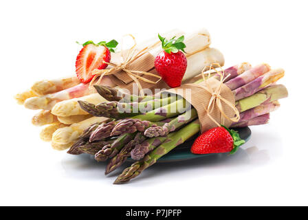 White and green asparagus with strawberries in front of white background - Stock Photo