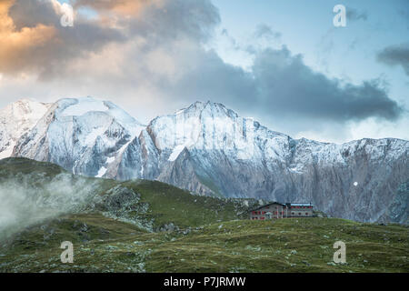 Pfitscherjochhütte (mountain lodge) with snow-capped mountains of Hochferner and Hochfeiler in the background, beautyful clouds, sunrise - Stock Photo