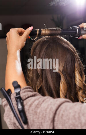 hairdresser making a hair curling to a client - Stock Photo