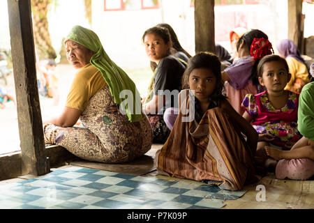 Young girl and other children and women in the port city of Singkil, Indonesia, - Stock Photo