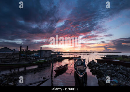 Fishing boats in the harbor of Haloban during sunset - Stock Photo