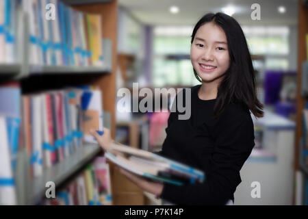 Asian female students holding for selection Book  in library - Stock Photo