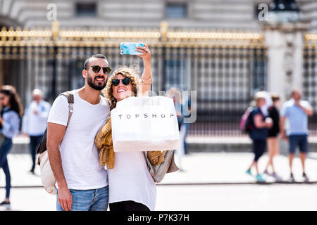 London, UK - June 21, 2018: Romantic young happy smiling couple standing taking selfie in front of gold, golden Buckingham Palace closeup fence, topsh - Stock Photo