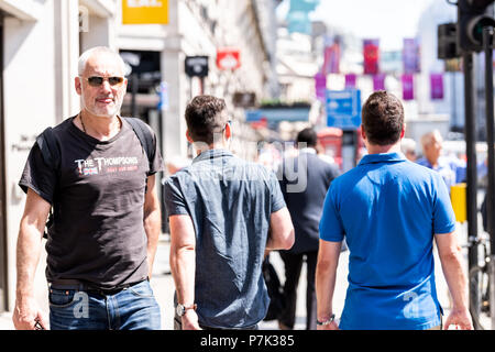 London, UK - June 22, 2018: Crowd of many people man pedestrians walking on Piccadilly sidewalk street road in center of downtown city, England flag o - Stock Photo