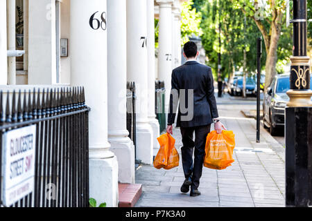 London, UK - June 22, 2018: Neighborhood district of Pimlico, Gloucester Street, businessman man carrying grocery shopping bags after work in evening  - Stock Photo