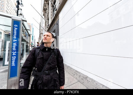 New York City, USA - April 7, 2018: Manhattan NYC midtown Herald Square, 6th avenue road, happy person man people pedestrians walking, looking up - Stock Photo