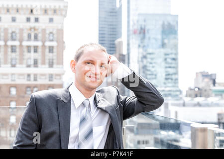 Handsome, attractive young happy smiling businessman closeup face portrait standing in suit, tie, by New York City cityscape skyline in Manhattan afte - Stock Photo