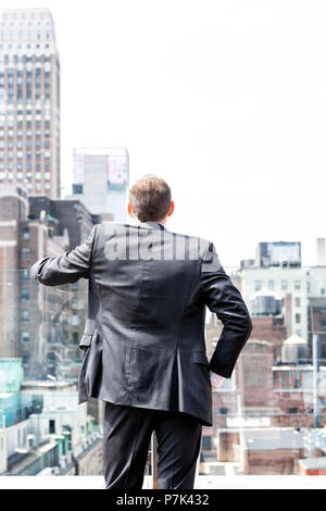 Back of young businessman standing in wrinkled business suit looking at New York City cityscape skyline in midtown Manhattan after interview break at  - Stock Photo