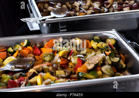 Fresh grilled vegetables in hot buffet tray with closeup of spoon to serve food to plate in banquet, wedding, or restaurant inside - Stock Photo