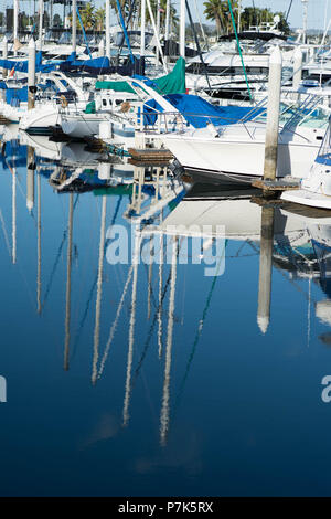 Reflections of Sailboats in the ocean marina at sunrise - Stock Photo