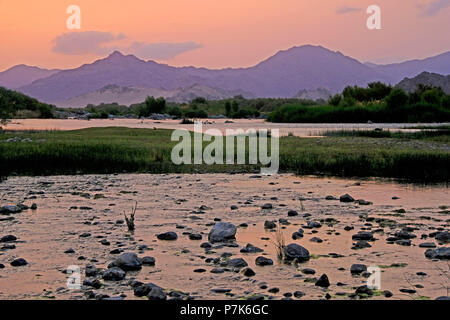 stony river bed of the Orange River / Oranjerivier (border river) in Richtersveld at evening mood, opposite side of Namibia, Namaqua, South Africa - Stock Photo