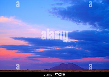 Evening mood after sunset with coloured clouds over a lonely, empty desert landscape with mountain in Namibia, Blue Hour, Dorob National Park - Stock Photo