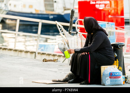Woman begging in black robe in the port of Chania, poverty, Europe, Crete, Greece - Stock Photo