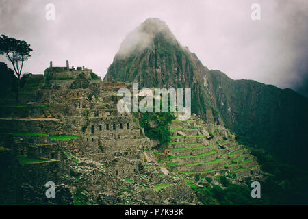 Beautiful wallpaper photo of Machu Picchu ruins and agriculture terraces with mountain with fog in the background. No people. - Stock Photo