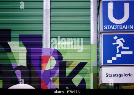 A square shaped sign of the light rail and subway system in front of the State gallery in Stuttgart next to a striking noise barrier wall, - Stock Photo