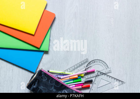 Colorful notebooks on white wooden background and pencil case with stationery - Stock Photo