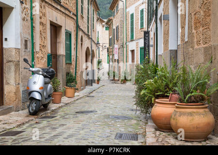 Parked scooter and potted plants in an alley in Fornalutx, Mallorca, Balearic Islands, Spain - Stock Photo