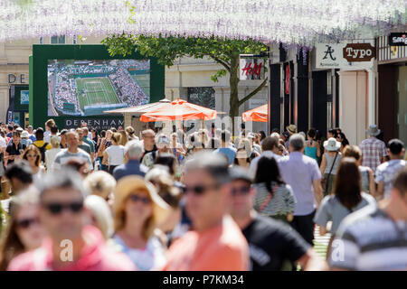 Bath, UK, 7th July, 2018. As Bath enjoys another very hot and sunny day shoppers are pictured enjoying the sunshine in SouthGate shopping centre where a big screen has been set up so that tennis fans can watch the Wimbledon tennis championship. Credit: lynchpics/Alamy Live News - Stock Photo