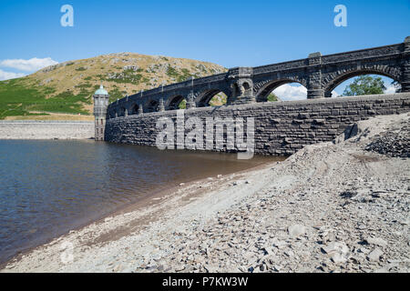 Craig Goch Dam, Wales, UK. 7th July 2018. Extremely low water levels revealing the shoreline due to the current hot weather in the UK, Normally water would be overflowing the arches generating electricity. The Dam normally when full has 2000 million gallons used to supply water to Birmingham along with other dams in the Elan valley. Credit: Bob Sharples/Alamy Live News - Stock Photo