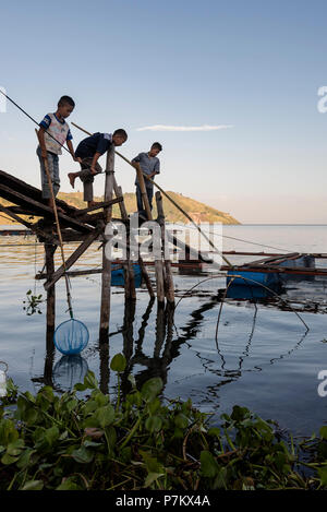 Children fishing on Lake Toba - Stock Photo