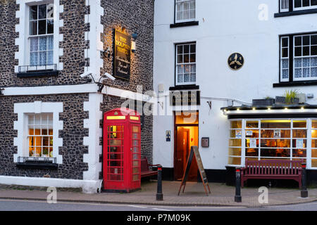 red telephone booth in front of The Dolphin Hotel, Beer, Devon, England, UK - Stock Photo