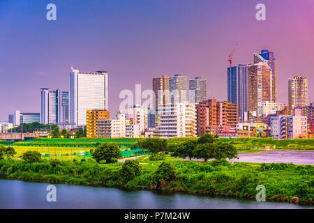 Kawasaki, Japan city skyline at dusk on the Tamagawa River. - Stock Photo