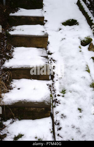 A snow-covered staircase with slippery steps. - Stock Photo